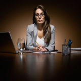 Serious businesswoman working late at desk. Serious, unhappy businesswoman working late at desk with laptop and paperwork Stock Images