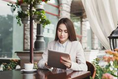 Young businesswoman outdoors working with laptop. Serious businesswoman working with tablet, drinking coffee, sitting at summer terrace cafe. Lifestyle portrait Stock Photography