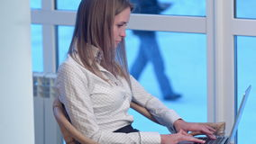 Serious businesswoman working typing on a laptop in a hotel. Professional shot in 4K resolution. 073. You can use it e.g. in your commercial video, business stock video footage