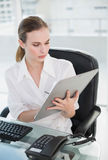 Serious businesswoman writing on clipboard sitting at desk Royalty Free Stock Photography