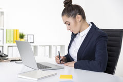 Serious businesswoman is writing a note Stock Photography