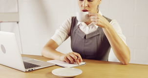 Serious businesswoman writing notes while drinking coffee stock video