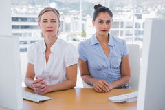 Serious businesswomen sitting side by side Royalty Free Stock Images