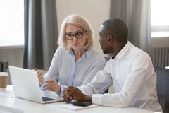 Free Serious Busy Aged Mentor Helping To New African Employee Stock Images - 160749394