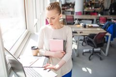 Serious and busy woman is looking to the laptop and using it. Also she holds some notebooks in her hands. Woman is. Wokring Royalty Free Stock Photography