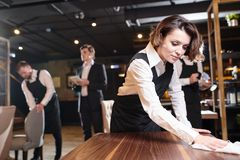 Busy waitress preparing restaurant for open and making cleanup. Serious busy young waitress and her colleagues preparing restaurant for open and making cleanup royalty free stock images