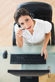 Serious call center agent looking at camera while on a call Stock Images