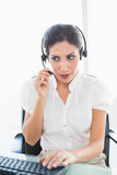 Serious call centre agent working at her desk on a call. In her office Stock Photos