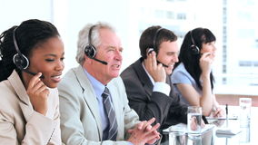Serious call centre agents talking with headsets Stock Images