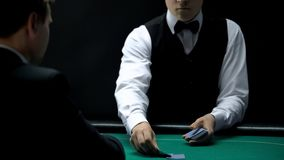 Serious casino croupier dealing cards for client on poker green table, gambling. Stock photo royalty free stock photos