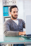 Serious casual businessman working on laptop at his desk Royalty Free Stock Photos