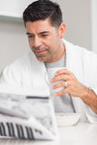 Serious casual man with coffee cup reading newspaper Stock Images