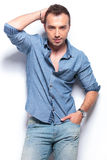 Serious casual man poses with hand on head and in pocket Royalty Free Stock Images