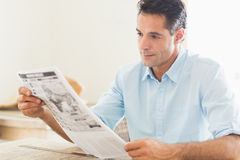 Serious casual man reading newspaper in kitchen Royalty Free Stock Photo