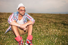Serious casual man sitting in a field Stock Photos