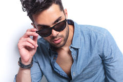 Serious casual man takes down his sunglasses Stock Image
