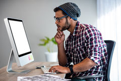 Serious casual man working at computer desk Stock Images