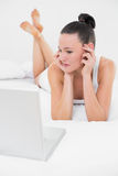 Serious casual woman looking at laptop in bed Stock Images