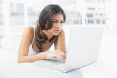 Serious casual woman using laptop in bed Royalty Free Stock Image