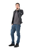 Serious casual young man in jeans and leather jacket talking on the cellphone. Full body length portrait isolated over white background Stock Photography