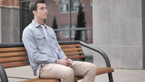 Serious casual young man sitting outdoor stock video