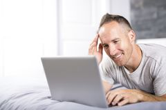 Serious casual young man using laptop in bed at home Stock Photos