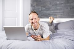 Serious casual young man using laptop in bed at home Royalty Free Stock Photo
