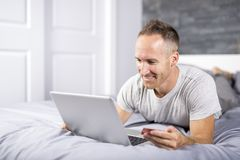 Serious casual young man using laptop in bed at home Stock Photo