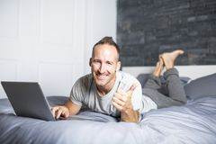 Serious casual young man using laptop in bed at home. A Serious casual young man using laptop in bed at home Stock Image