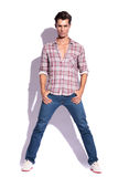 Model poses with hands in pockets. Serious casual young model standing with thumbs in pockets and legs spread is looking at the camera. isolated on white, with Stock Image