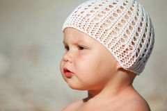 Serious Caucasian baby girl in white hat Stock Images