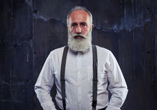 Serious Caucasian bearded man standing in studio  over b Stock Images