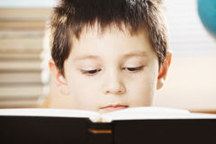 Serious caucasian boy reading book closeup Royalty Free Stock Photos