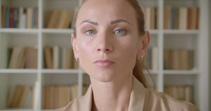 Serious caucasian businesswoman watching leftwards beind interested and attentive on bookshelves background. Serious caucasian businesswoman watching leftwards stock video