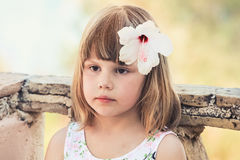 Serious Caucasian little girl with white flower Royalty Free Stock Image