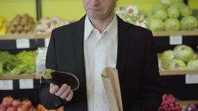 Serious Caucasian man in suit smelling eggplant, putting it into paper pack and leaving. Young businessman purchasing