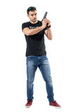 Serious cautious policeman in plain clothes holding gun with both hands. Royalty Free Stock Photos