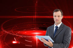 Serious charismatic businessman holding a tablet computer Stock Photo