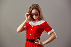Serious charming mrs.Santa Claus in sunglasses dressed in the red robe and white gloves stands on the gray background. stock image