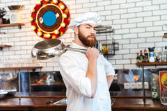 Serious chef cook standing and holding frying pan Royalty Free Stock Photo