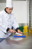 Serious chef cutting raw salmon with knife on blue cutting board Royalty Free Stock Images