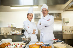 Serious chef and head chef standing arms crossed. In professional kitchen royalty free stock photography