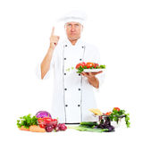 Serious chef holding plate with vegetables Stock Image