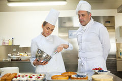 Serious chef whisking while being watched by head chef Stock Photos