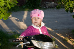 Serious child. On the moped Royalty Free Stock Image