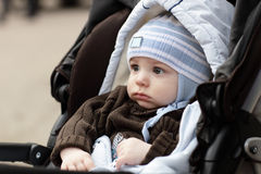 Serious child. The serious child is sitting in stroller royalty free stock photography