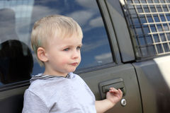 Serious child and car Royalty Free Stock Images