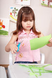 Serious child cutting paper. Stock Photo
