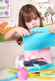 Serious child cutting paper. Stock Photos