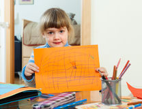 Serious child with drawed paper. In home interior Stock Photos